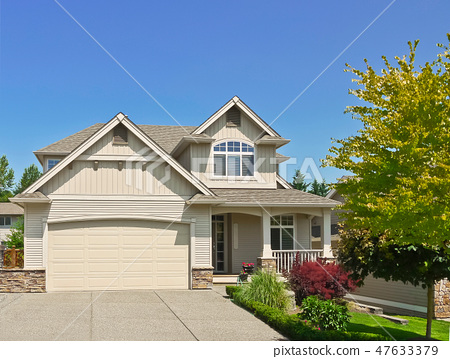 Modest family house with concrete driveway to the garage on blue sky background 47633379