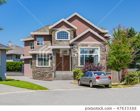 Luxury family house with a car parked on concrete driveway in front 47633388