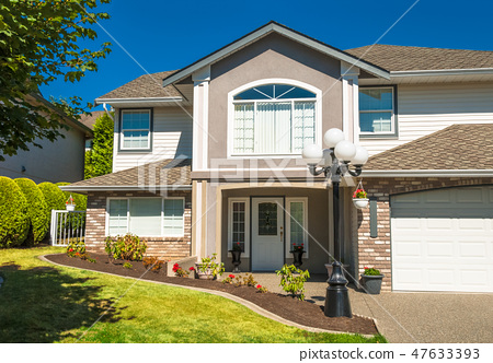 Main entrance of luxury house with flowerbed and grass lawn in front 47633393
