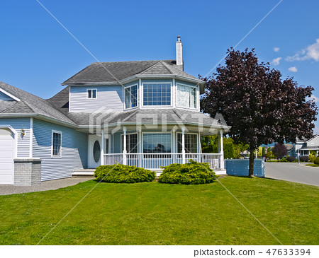 Large residential house with rounded porch and big green lawn at the entrance 47633394