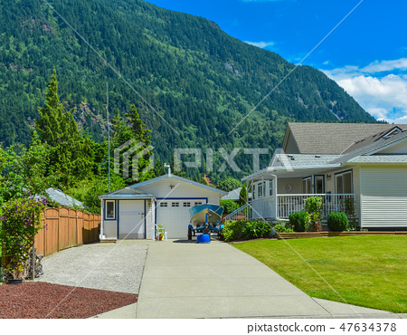 Residential house with garage on the back yard and small boat parked near by 47634378