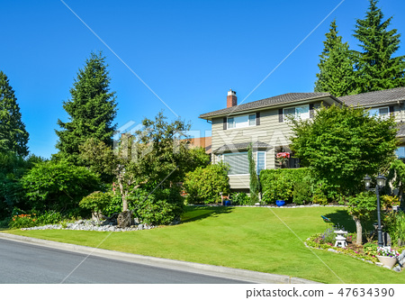 Green lawn on front yard of residential house on the street 47634390