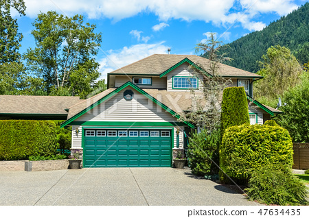 Big family house with wide concrete driveway and green wide garage door 47634435