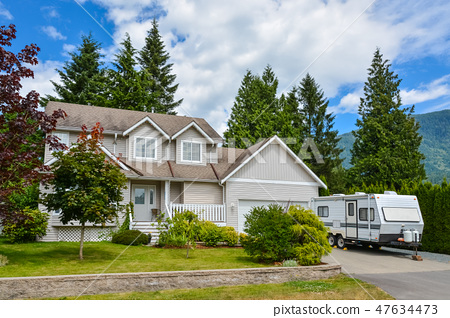 Big family house on country side with RV trailer parked on driveway 47634473