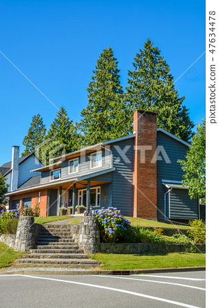 Big residential house with steps leading to front yard on land terrace 47634478