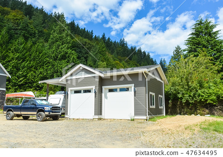Brand detached double garage with car and boat parked on gravel driveway 47634495