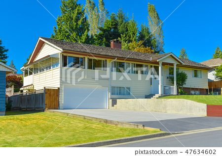 Expanded family house with concrete driveway and mowed lawn on the front yard 47634602