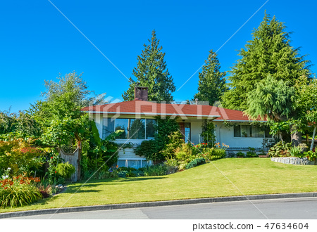 Family house with big front yard immersed in the green 47634604