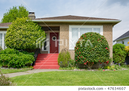Main entrance of residential house with concrete pathway over the front yard 47634607