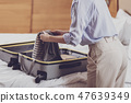 Close up of optimistic woman folding her suitcase 47639349