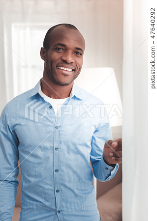 Delighted nice man standing near the curtain 47640292
