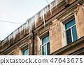 roofs of houses and windows in huge hanging icicles  47643675