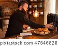 Beaded hipste waiter preparing cofffe behind the bar. 47646828