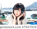 A young woman listening to music 47647936