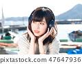 一个年轻的女人,听听音乐 47647936