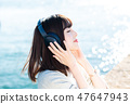 A young woman listening to music 47647943