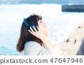 A young woman listening to music 47647946