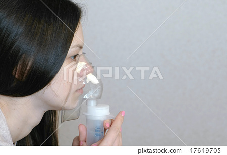 Use nebulizer and inhaler for the treatment. Young woman inhaling through inhaler mask. Closeup side 47649705