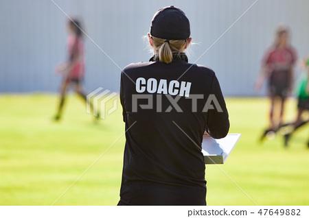 Back of female sport coach wearing COACH shirt 47649882