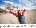 Portrait of pretty woman tourist standing on the sandy beach near volleyball net during hot summer 47652454
