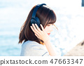 A young woman listening to music 47663347
