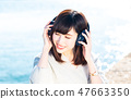 A young woman listening to music 47663350