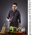 Man prepares a delicious dish on a gray background. 47670457