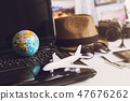 Toy airplane on laptop keyboard with globe 47676262