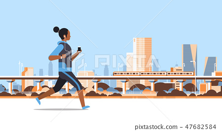 fitness woman running outdoor african girl listening to music with headphones on smartphone healthy 47682584