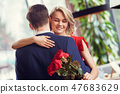 Young couple on date in restaurant dancing holding bouquet woman closed eyes joyful 47683629
