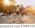 Friends ride on carts, near the supermarket 47684729