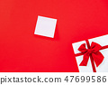 Empty notepaper on red background with gift box 47699586