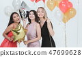 Young women have fun together at party. 47699628