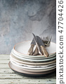Stack of plates with cutlery 47704426