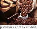 Fresh roasted coffee beans in burlap sack, coffee cup and grinder on dark background. 47705644