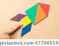Color tangram in rocket shape and hand at the base 47706559