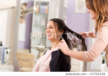 Smiling woman combing hair after wash 47708166