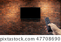Television on brick wall with hand using remote 47708690