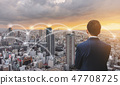 Businessman in blue suit with cityscape in sunset 47708725