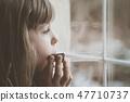 Sad girl playing harmonica by the window 47710737