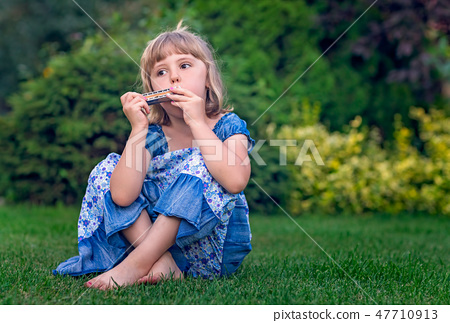 Cute girl playing harmonica in the garden 47710913