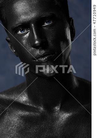 a man in black make-up. portrait in dark paint 47710949