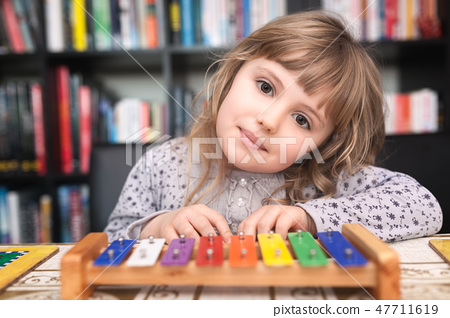 Cute little girl playing colorful cymbals 47711619