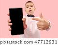 Indoor portrait of attractive young boy holding blank smartphone 47712931