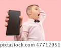 Indoor portrait of attractive young boy holding blank smartphone 47712951