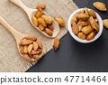 Almonds in a black bowl against dark rustic 47714464