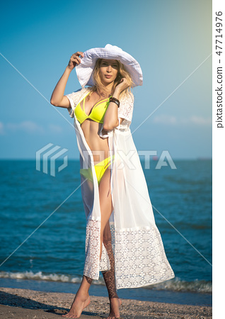 Gorgeous girl model on the beach on seaside in yellow swimsuit, white dress and big round hat 47714976
