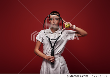 Refuse to Lose! Young tennis player standing isolated over red background with a racket and a ball 47723805