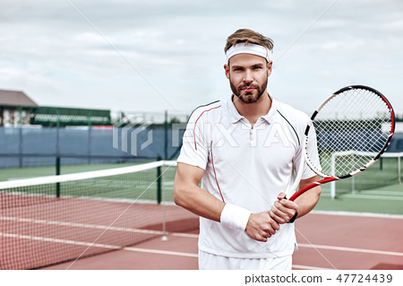 Never give up. Handsome man standing on the tennis court. 47724439