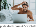 Relaxed guy using laptop in bed in morning 47729940